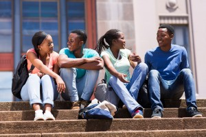 group of african american college friends sitting on stairs